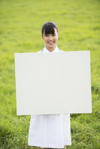 草原でホワイトボードを持つ看護師の写真素材 [FYI04558162]