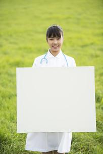 草原でホワイトボードを持つ看護師の写真素材 [FYI04558163]