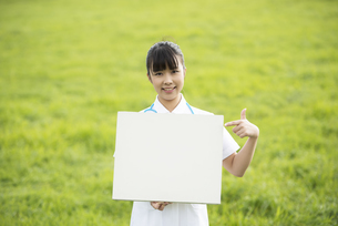草原でホワイトボードを指差す看護師の写真素材 [FYI04558165]