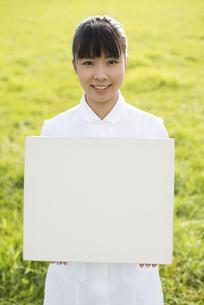 草原でホワイトボードを持つ看護師の写真素材 [FYI04558172]