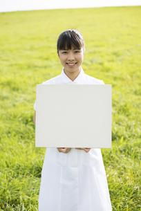 草原でホワイトボードを持つ看護師の写真素材 [FYI04558174]