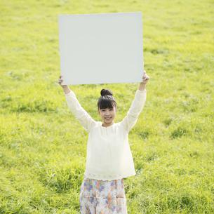 草原でホワイトボードを掲げる女性の写真素材 [FYI04558191]