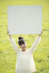 草原でホワイトボードを掲げる女性の写真素材 [FYI04558195]