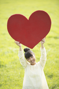 草原で赤いハートを持つ女性の写真素材 [FYI04558199]