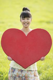 草原で赤いハートを持つ女性の写真素材 [FYI04558202]
