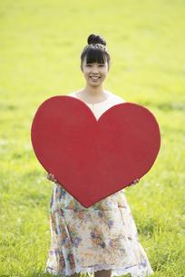 草原で赤いハートを持つ女性の写真素材 [FYI04558203]