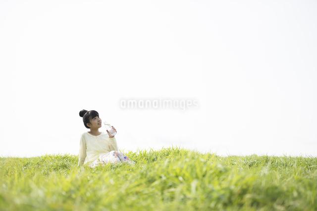 草原で水分補給をする女性の写真素材 [FYI04558205]