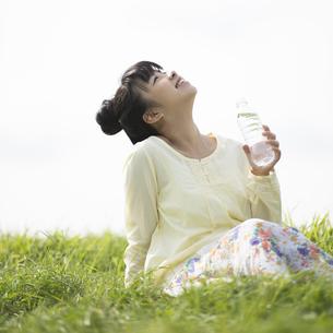 草原で水分補給をする女性の写真素材 [FYI04558215]