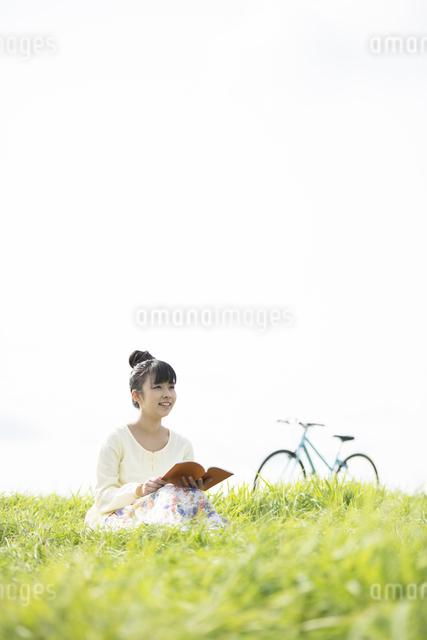 草原で本を読む女性の写真素材 [FYI04558222]