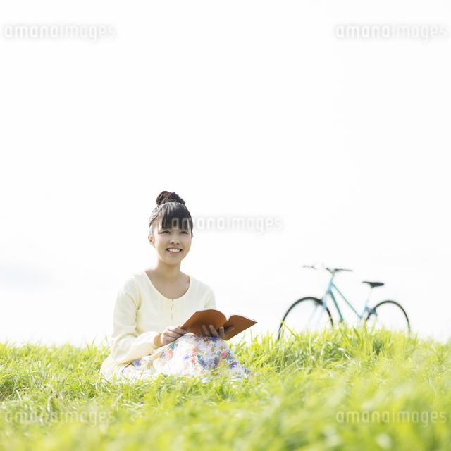 草原で本を読む女性の写真素材 [FYI04558223]