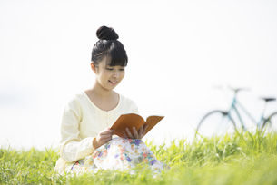 草原で本を読む女性の写真素材 [FYI04558227]
