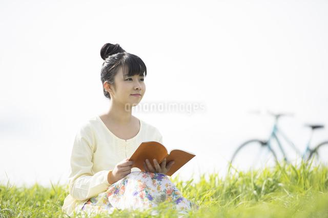 草原で本を読む女性の写真素材 [FYI04558229]