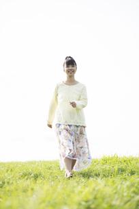 草原を歩く女性の写真素材 [FYI04558232]