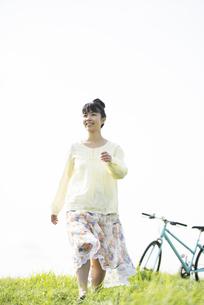 草原を歩く女性の写真素材 [FYI04558235]