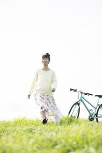 草原を歩く女性の写真素材 [FYI04558236]