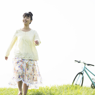 草原を歩く女性の写真素材 [FYI04558241]