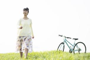 草原を歩く女性の写真素材 [FYI04558243]