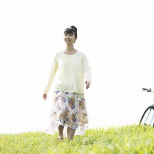 草原を歩く女性の写真素材 [FYI04558244]