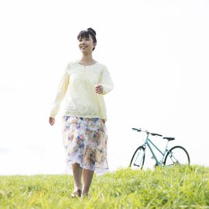 草原を歩く女性の写真素材 [FYI04558247]