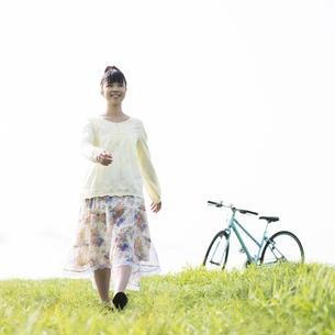 草原を歩く女性の写真素材 [FYI04558248]