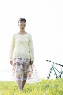 草原を歩く女性の写真素材 [FYI04558250]