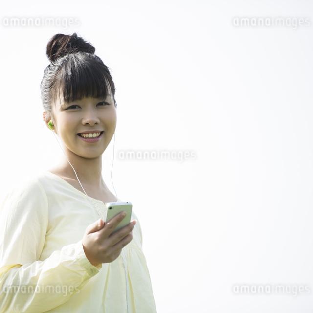 スマートフォンで音楽を聴く女性の写真素材 [FYI04558257]
