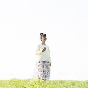 草原で音楽を聴く女性の写真素材 [FYI04558258]