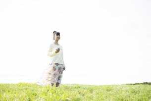 草原で音楽を聴く女性の写真素材 [FYI04558260]