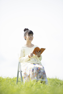 草原で本を読む女性の写真素材 [FYI04558277]