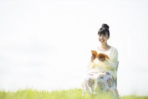 草原で本を読む女性の写真素材 [FYI04558287]
