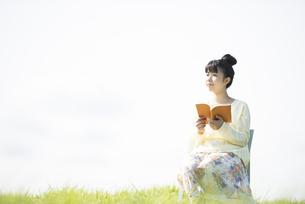 草原で本を読む女性の写真素材 [FYI04558288]