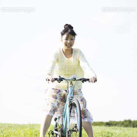 草原で自転車に乗る女性の写真素材 [FYI04558289]