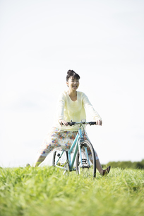 草原で自転車に乗る女性の写真素材 [FYI04558290]