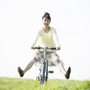 草原で自転車に乗る女性の写真素材 [FYI04558291]