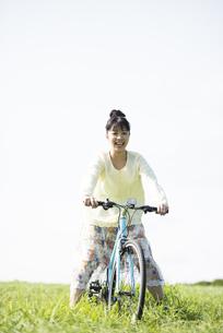 草原で自転車に乗る女性の写真素材 [FYI04558292]