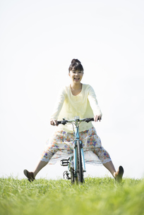 草原で自転車に乗る女性の写真素材 [FYI04558293]
