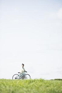 草原で自転車を押す女性の写真素材 [FYI04558294]