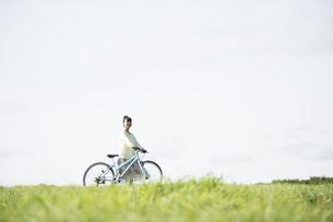草原で自転車を押す女性の写真素材 [FYI04558295]