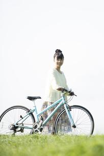 草原で自転車を押す女性の写真素材 [FYI04558296]