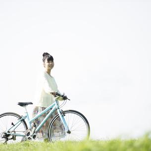 草原で自転車を押す女性の写真素材 [FYI04558297]