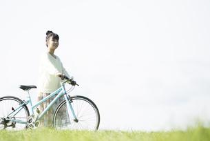 草原で自転車を押す女性の写真素材 [FYI04558299]