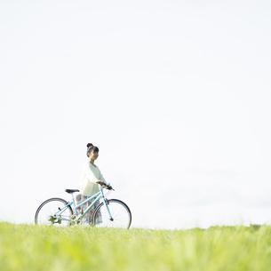 草原で自転車を押す女性の写真素材 [FYI04558300]