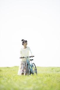 草原で自転車を押す女性の写真素材 [FYI04558303]
