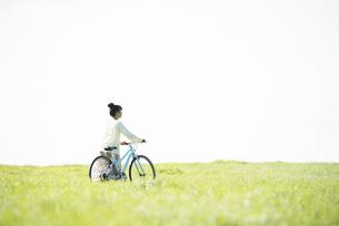 草原で自転車を押す女性の後姿の写真素材 [FYI04558305]