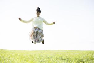 草原でジャンプをする女性の写真素材 [FYI04558306]