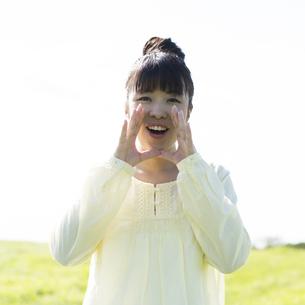 草原で口元に手をあてる女性の写真素材 [FYI04558313]