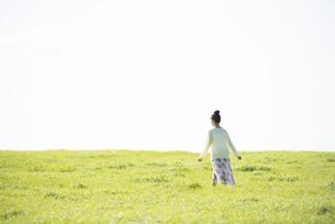 草原を歩く女性の後姿の写真素材 [FYI04558331]
