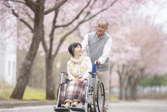 車椅子で散歩するシニア夫婦の写真素材 [FYI04558371]