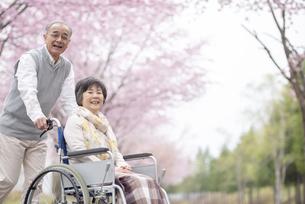 車椅子で散歩するシニア夫婦の写真素材 [FYI04558374]