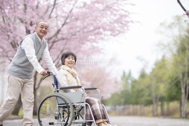 車椅子で散歩するシニア夫婦の写真素材 [FYI04558375]